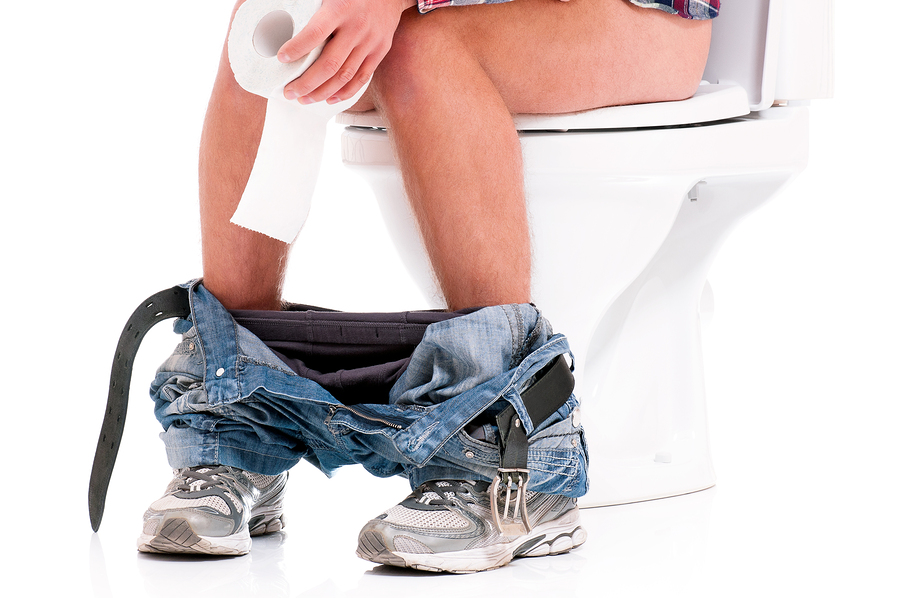 Man is sitting on the toilet bowl, holding paper in hands, on wh